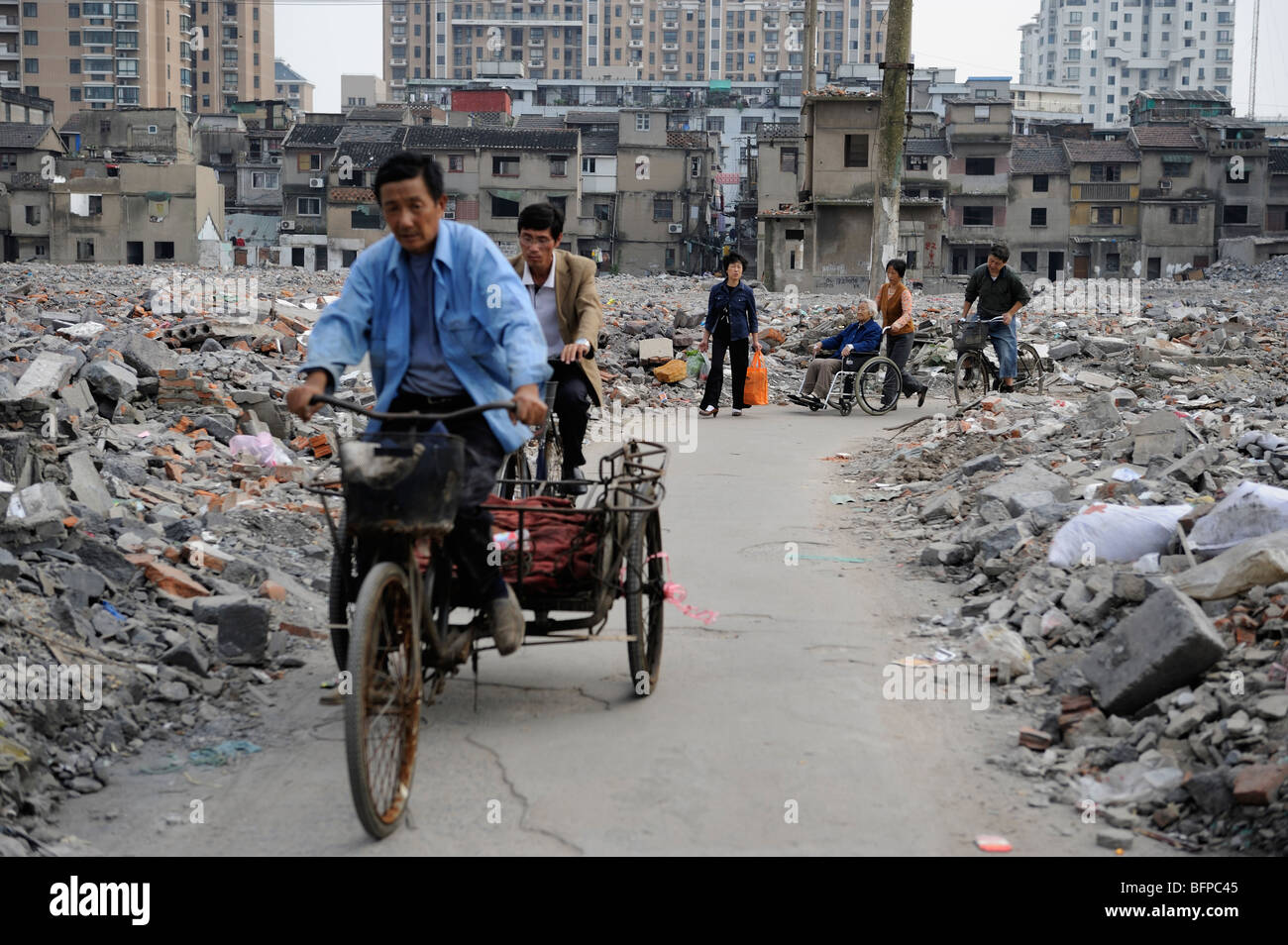 People through ruins of dilapidated residential area in ...