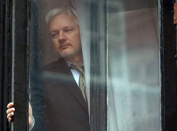 Julian Assange looking out a window quite sad