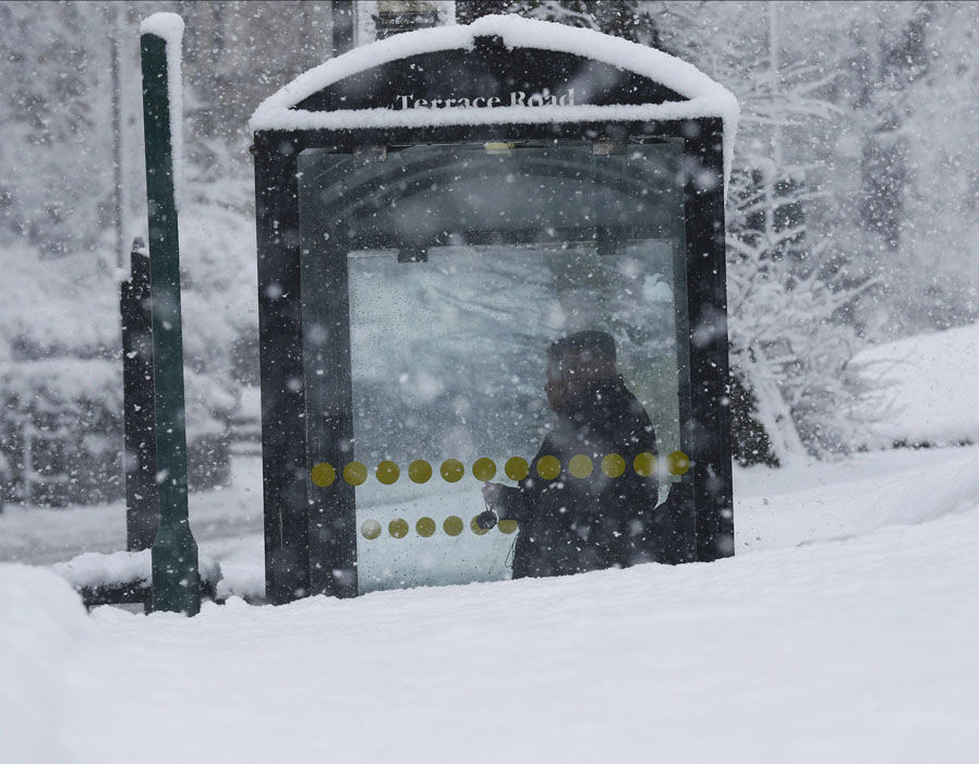People stand in a bus stop shelter during snowfall in Buxton | Britain ...