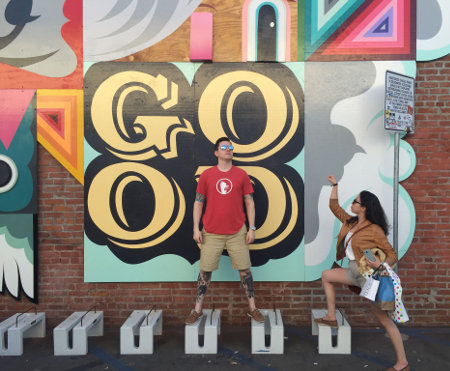 Two people posing in front of a mural.