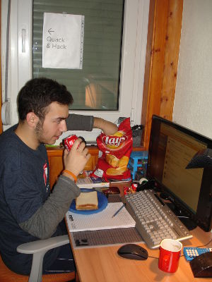 A developer wearing a DuckDuckGo t-shirt eating potato chips and a sandwich, drinking Coke while checking the computer screen.