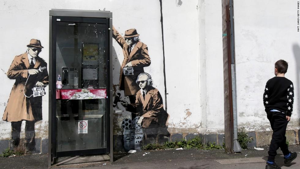 boy walks past graffiti street art believed to be by Banksy in April ...