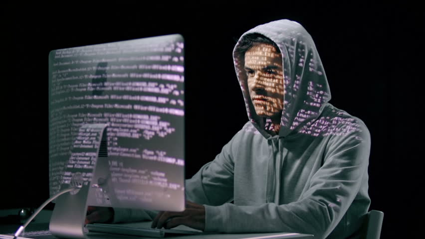 Hacker In Hoodie Computing With Projections On His Face ...