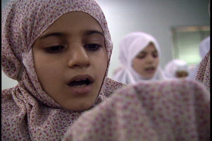 ... Girl in floral hijab recites the Koran in class at the Refi School