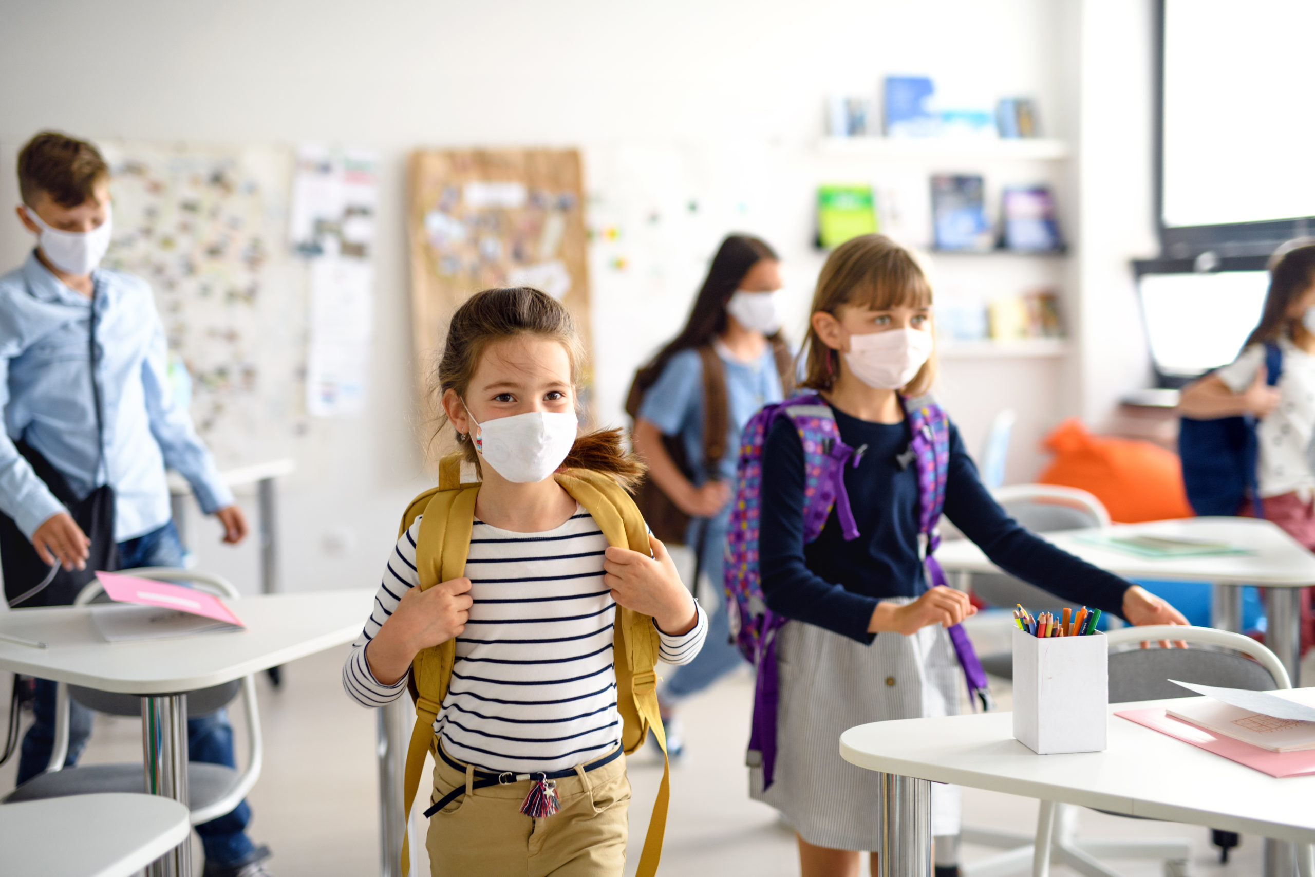 Group of children with face mask back at school after ...