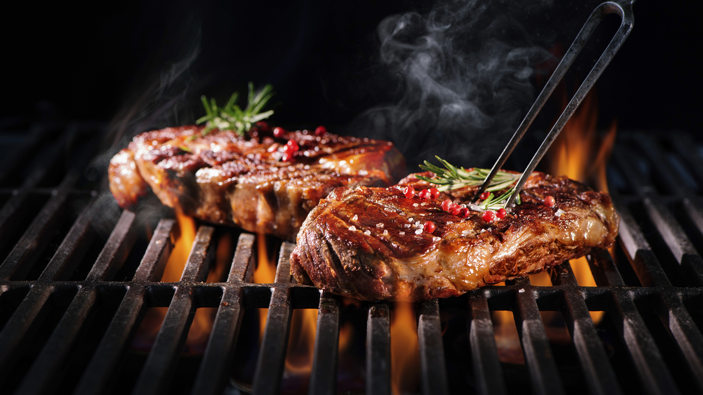 steaks on a grill using a fork accessory over open flames