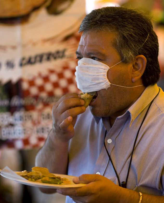 A man eats a taco while wearing a facial mask. - ABC News ...