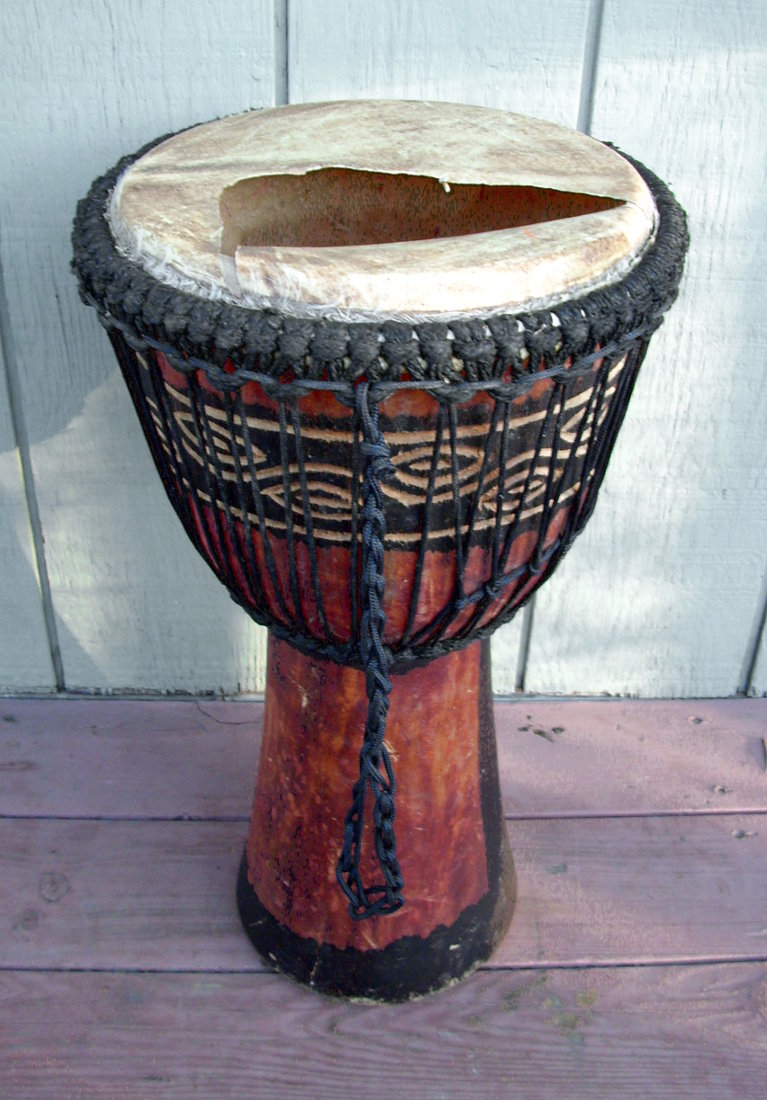 African djembe with a ripped drum head.