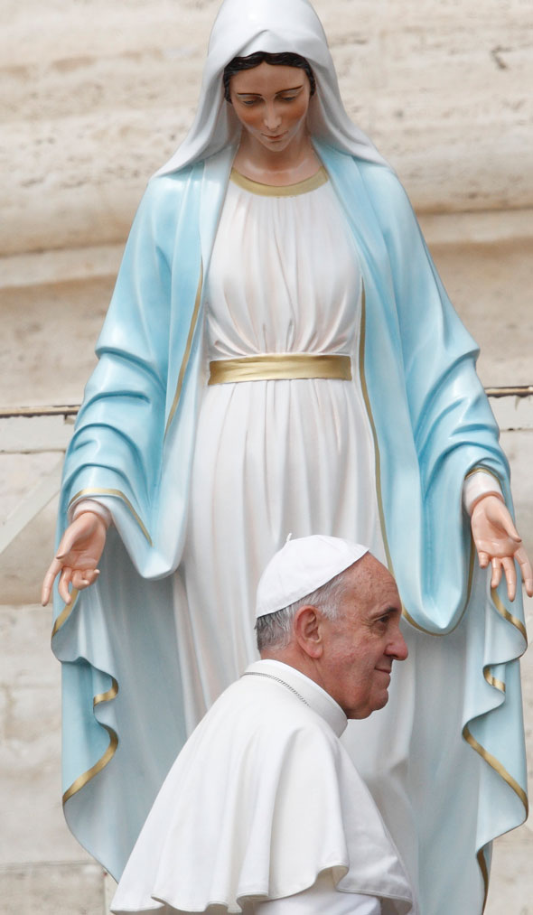 Pope Francis walks past a statue of Mary after praying in front of it ...