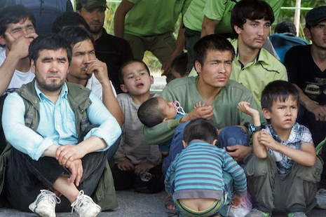 Asylum seekers thought to be from China's Uyghur minority sit before boarding trucks as Thai Immigration officials (not pictured) escort them to a court in Songkhla, southern Thailand on March 15, 2014 (AFP Photo/Tuwaedaniya Meringing)