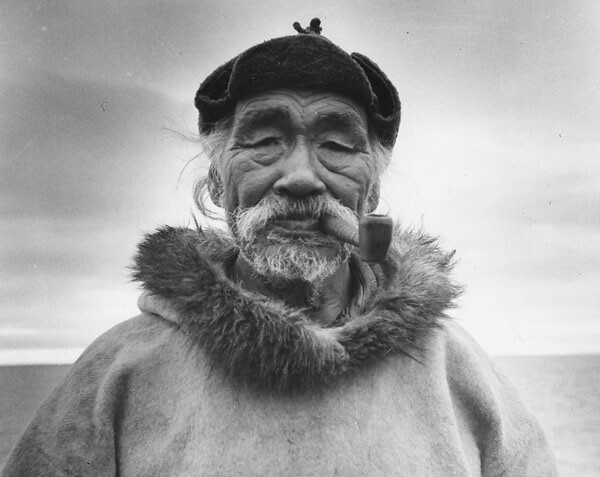 An elderly Inuit man, Aarulaq, wearing a duffle parka and ...