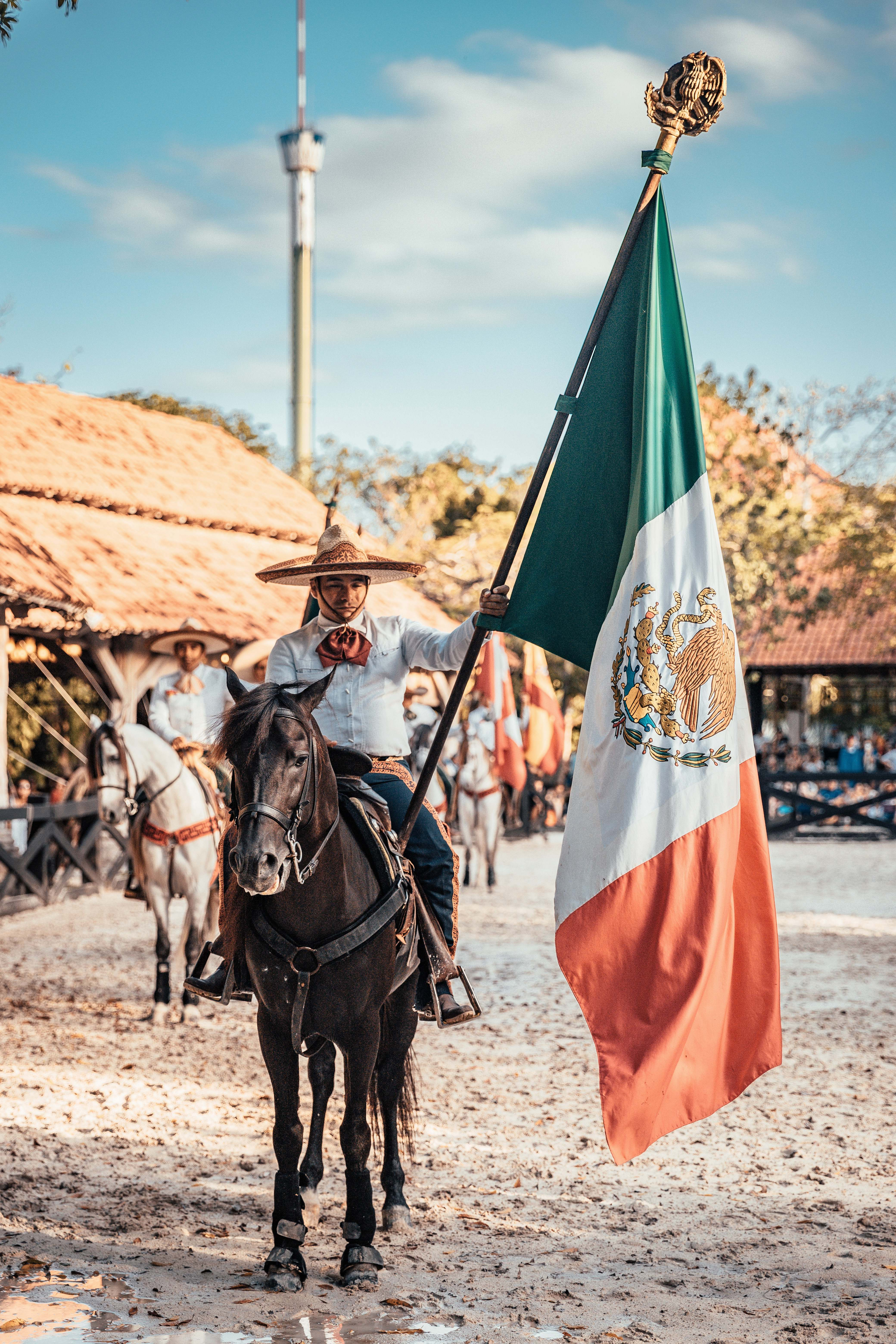 symbol man riding on horse while holding flag of Mexico ...
