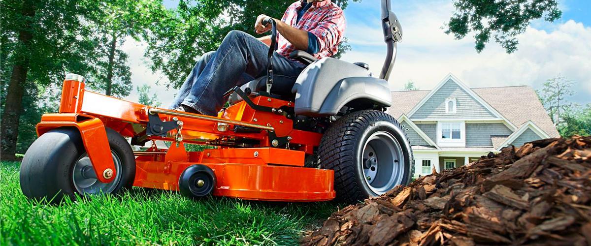 man on a Husqvarna riding mower mowing a lawn