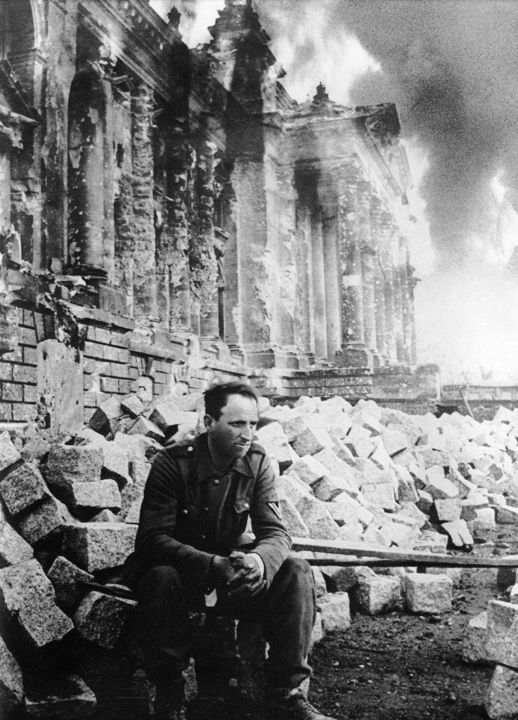 A defeated German soldier sits in front of a burning ...