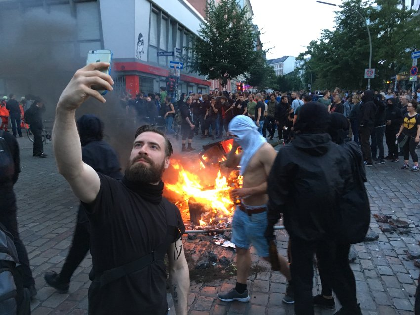 Antifa member taking a selfie in front of a burning ...