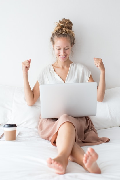 Cheerful girl working on laptop on bed Photo | Free Download