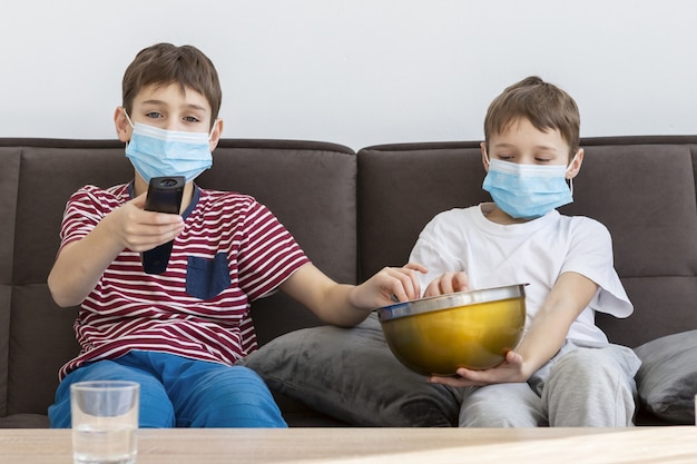 Children with medical masks watching tv and eating popcorn ...