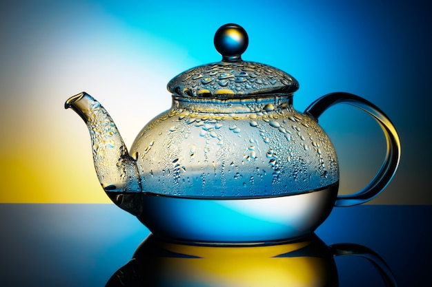 Glass teapot with boiling water and drops of condensation ...