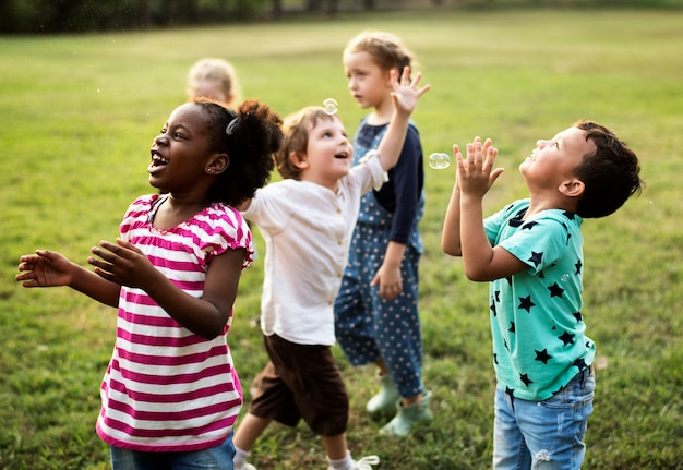 Group of diverse kids playing at the field together Photo ...