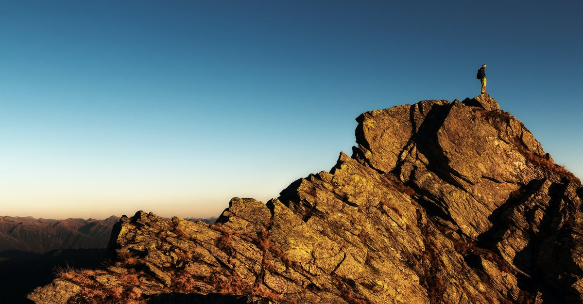 Man Standing on Top of Rock at Daytime · Free Stock Photo