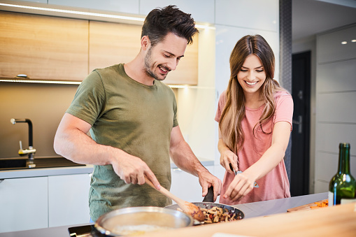 Cheerful Young Couple In The Kitchen Cooking Together And Having Fun Spending Time Together ...