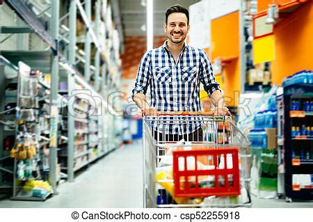 Handsome man shopping in supermarket pushing trolley.