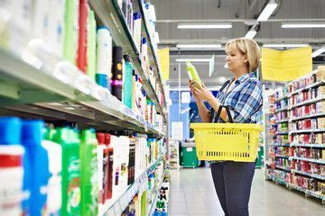 Woman chooses shampoo in cosmetics department   In ...