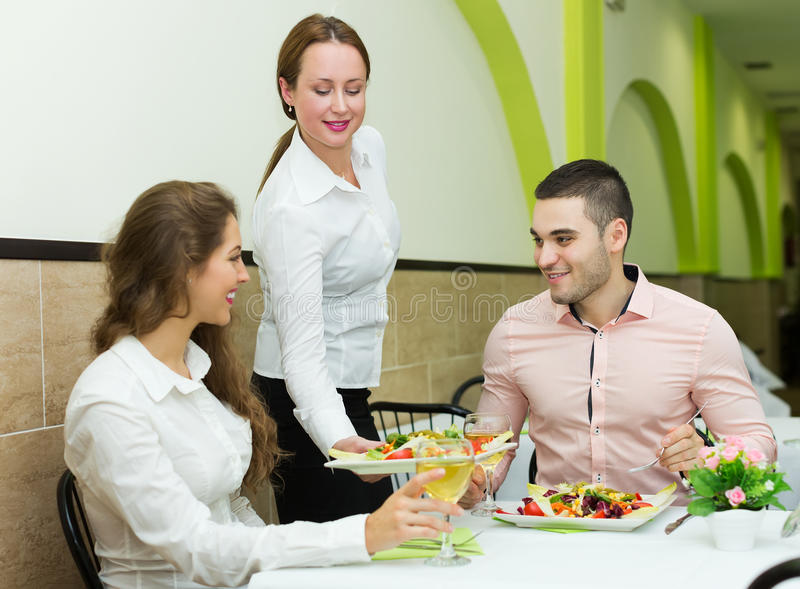waitress-serving-food-to-visitors-positi